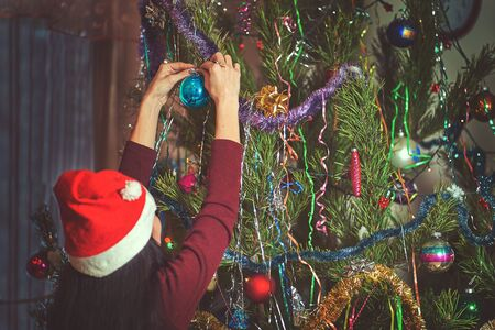 Girl in santa claus hat decorates christmas tree. Stok Fotoğraf