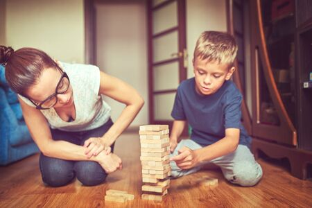 portrait of happy family playing jenga game at home