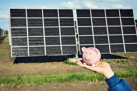 Hand holding money banknote with photovoltaic solar energy panels in background, 스톡 콘텐츠