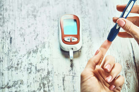 Close-up Of A Women's Hand Checking Blood Sugar Level With Glucometer