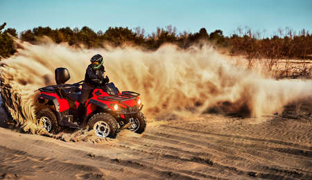 Teen riding ATV in sand dunes making a turn in the sand