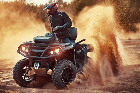 Teen riding ATV in sand dunes making a turn in the sand Reklamní fotografie