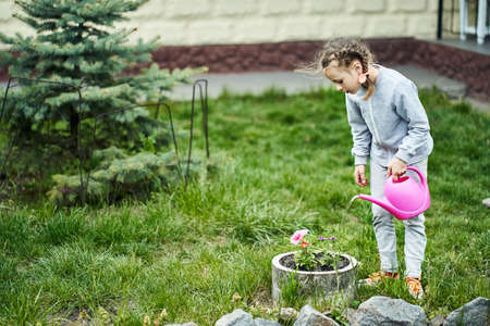 Child girl watering flowers in garden from can 스톡 콘텐츠