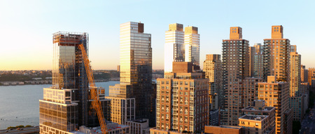 Manhattan Skyline on West Side, New York City and Hudson River at Sun Set with NYC Apartment buildings.