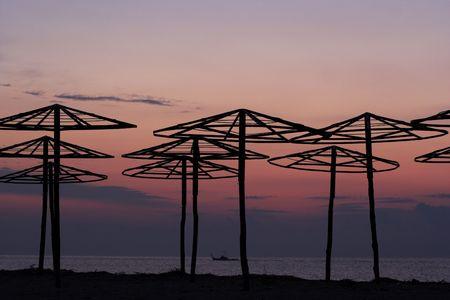 silhouettes of beach umbrellas at sunrise photo