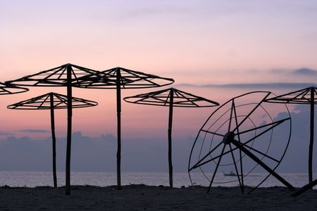 silhouettes of beach umbrellas at sunrise photo