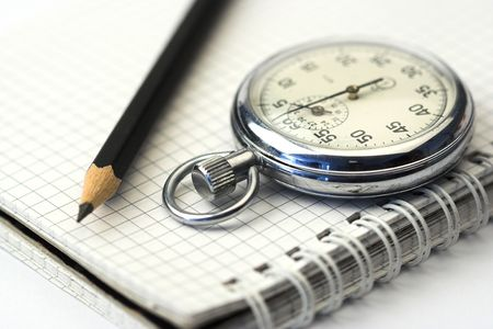 chronometer and black  pen over notebook