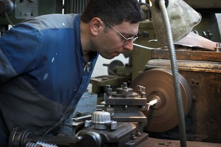 Worker and old gear in vintage workshop photo
