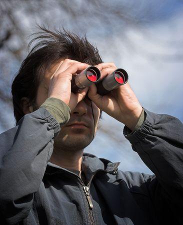 to observer: Man look through the  binoculars Stock Photo