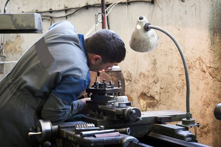 Worker and old gear in vintage workshop Stock Photo
