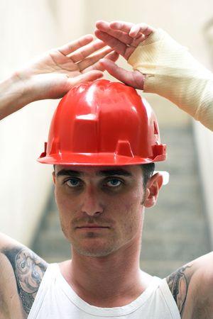 luxacion: tatuada hombre con casco rojo y la mano de yeso Foto de archivo