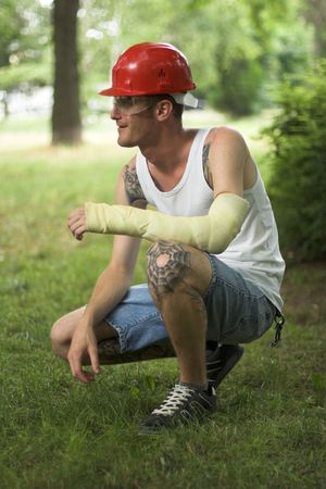 tattooed man with red helmet and hand in plaster Stock Photo - 3295132