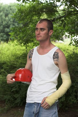 wroth: tattooed man with red helmet and hand in plaster Stock Photo