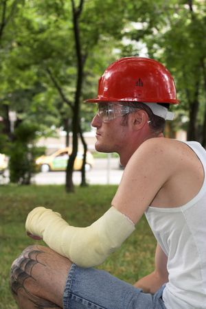dislocation: tattooed man with red helmet and hand in plaster Stock Photo