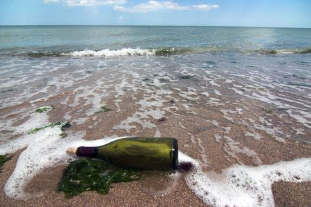 Message in the bottle on lonely beach photo