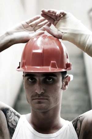 luxacion: tatuada hombre con casco rojo y yeso en la mano