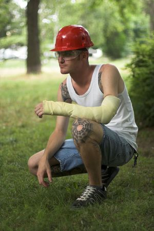 dislocation: ed man with red helmet and hand in plaster