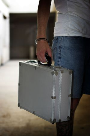Tattooed man with a briefcase and handcuffs Stock Photo - 3478770