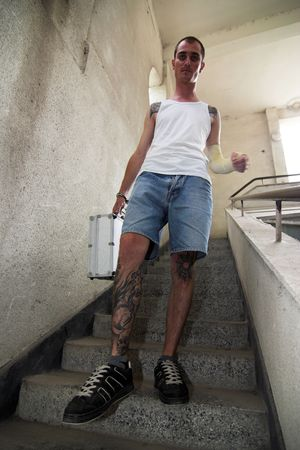 Tattooed man with a briefcase and handcuffs Stock Photo - 3478395