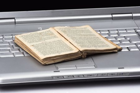 open old book over computer keyboard.