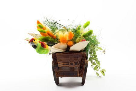 dried flower arrangement: arrangement of dry grass in small wooden  wheelbarrow