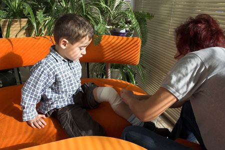 mother bandages a little boys leg