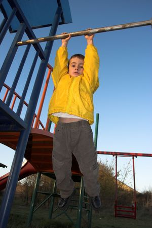 jungle gym: young boy climbing on jungle gym