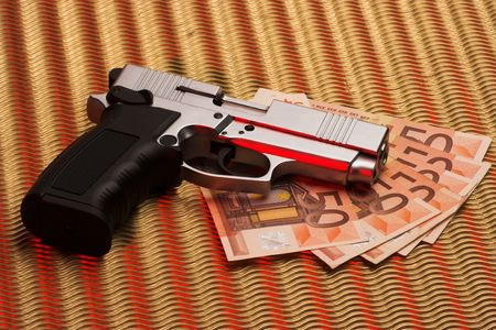 pistol over euro bills closeup photo