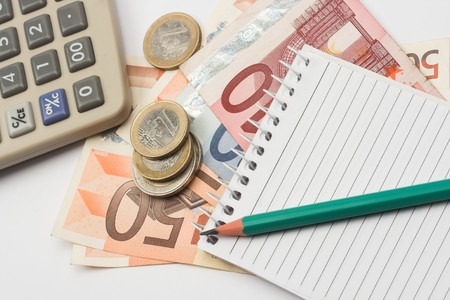 Euro bills,pen and calculator close up