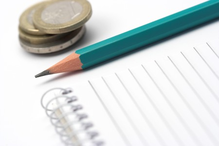 green pen,coins and notebook close up shallow DOF photo