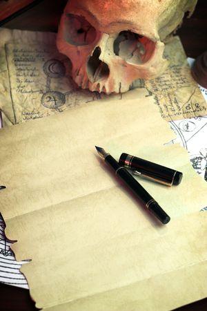 Un foglio di carta bianca e pen.The scrivania di un alchimista