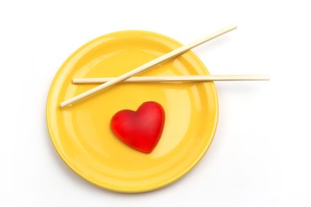 Heart in yellow plate and Chinese sticks photo