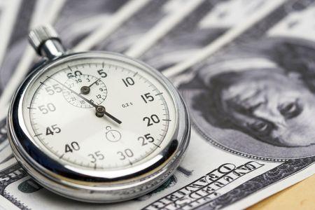 Chronometer and dollar bills close up photo