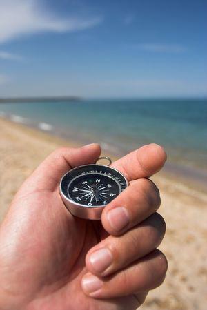bussola in mano, la spiaggia in background