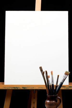 canvas,brushes and easel in black background  photo