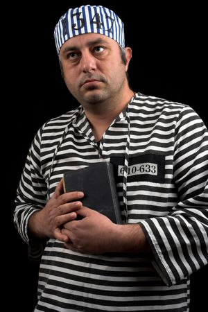 portrait of prisoner with book over black Imagens