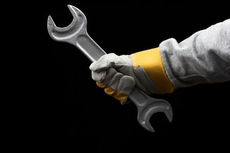 man holding a big wrench over black