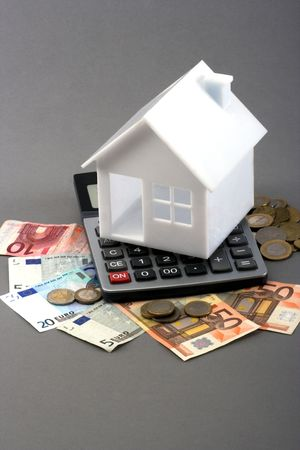 House on top of a calculator and money over gray background photo