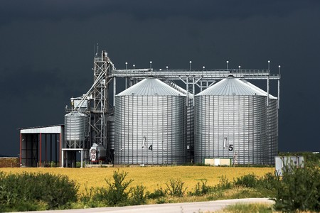 View of grain silos against stormy sky photo