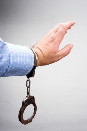 manacles: Handcuffs on the mans hand