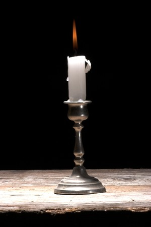 holder: glowing candle on a table, over black