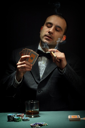 gamble: Portrait of a poker player over black background