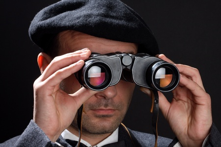 oversee: Old fashioned man looking through the binoculars