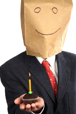 Businessman with paper bag on his head celebrating a birthday  Stock Photo