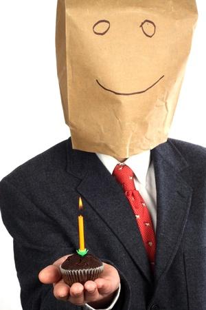 Imprenditore con un sacchetto di carta sulla sua testa festeggiare un compleanno