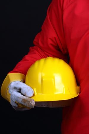 health industry: man holding yellow helmet over black background
