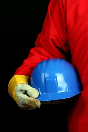 accident at work: man holding blue helmet over black background