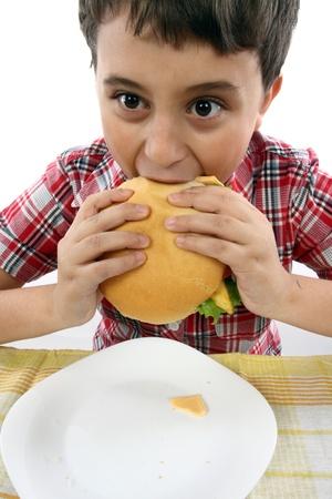 boy eating a big hamburger close up