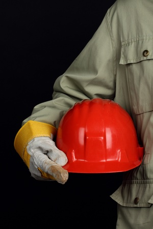 health dangers: man holding red helmet over black background  Stock Photo