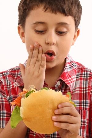 boy eating a big hamburger close up  photo